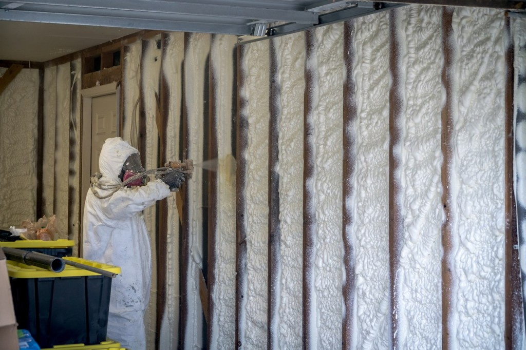 Worker spraying closed cell spray foam insulation on a home that was flooded by Hurricane Harvey
